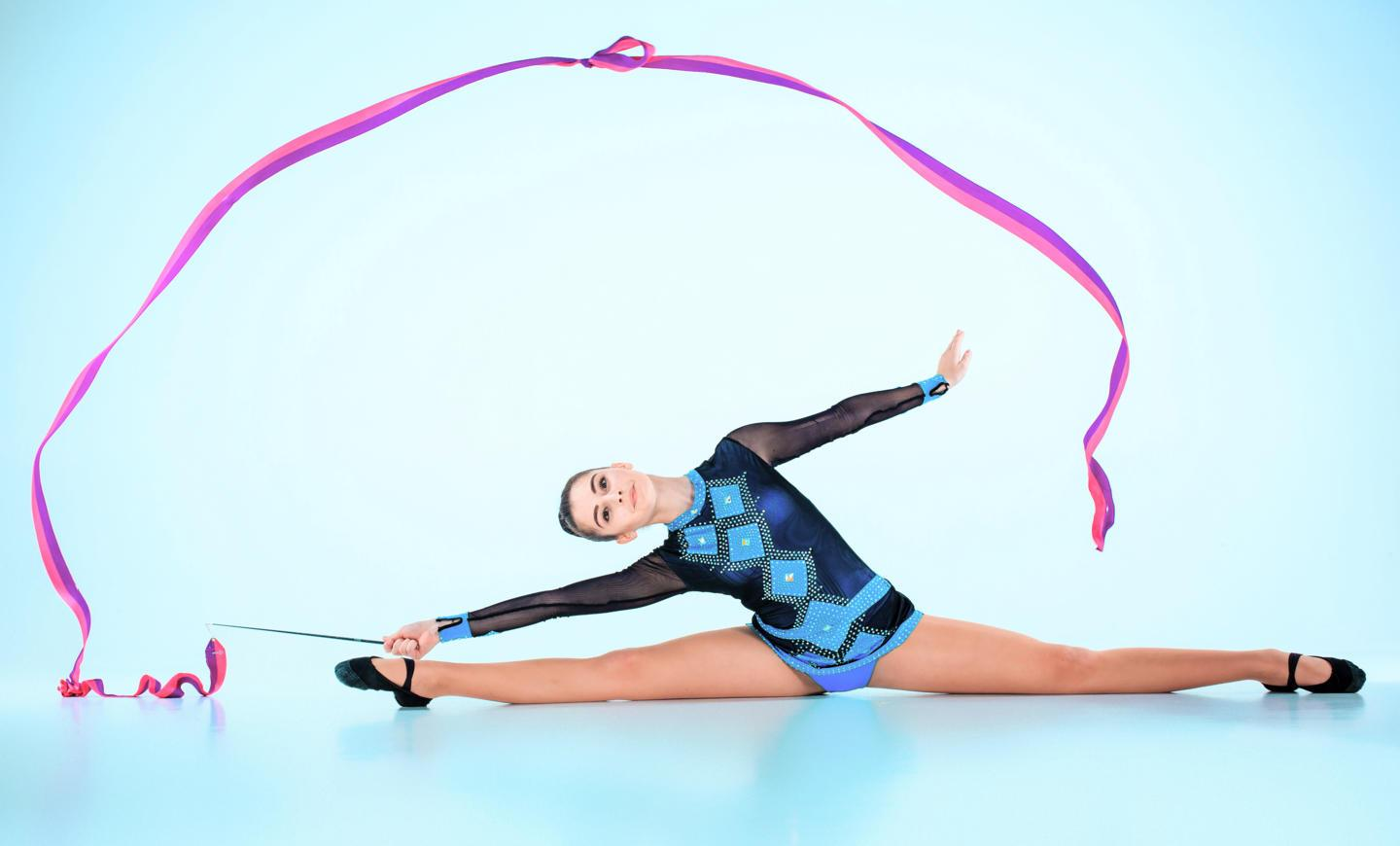 girl-doing-gymnastics-dance-with-colored-ribbon-blue-space.jpg