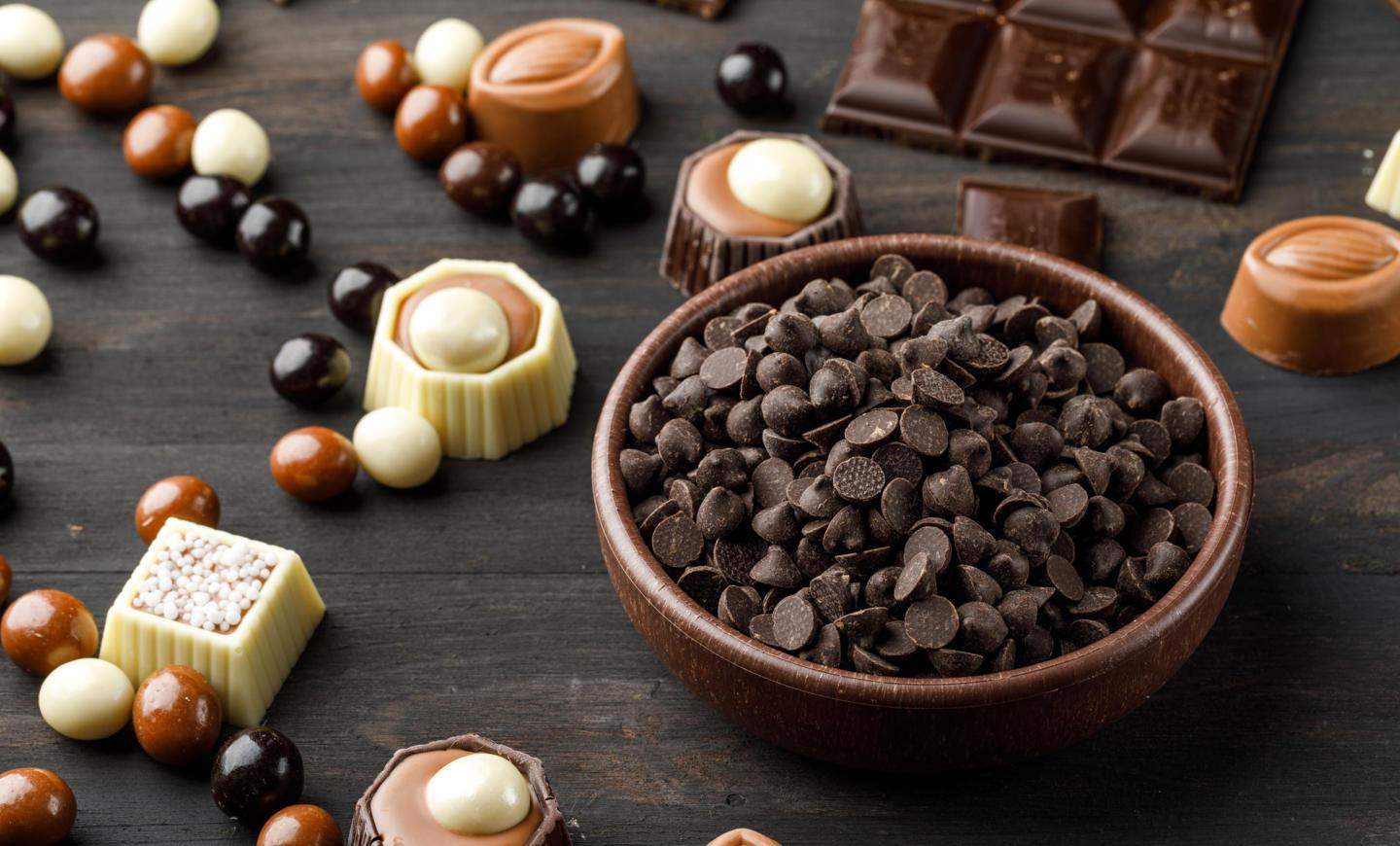 choco-drops-with-chocoballs-choco-bars-caramel-clay-bowl-wooden-table.jpg